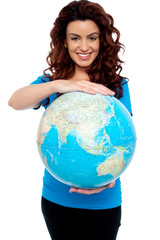 Cheerful girl holding globe safely with both hands