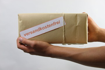 Mann hält versandkostenfreies Paket
