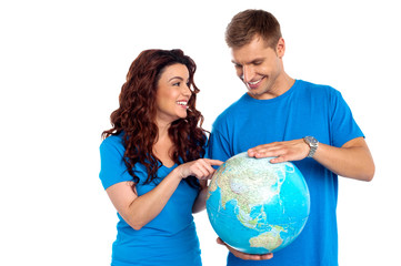 Couple discussing about specific country while points at it