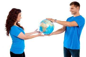 Causal young couple holding globe together