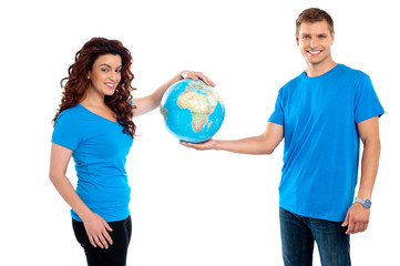 Attractive young couple holding a globe together