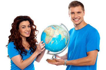 Joyful couple holding globe and smiling at camera