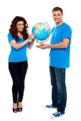 Full length of a couple holding globe over white