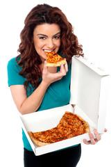 Young cheerful girl enjoying pizza alone