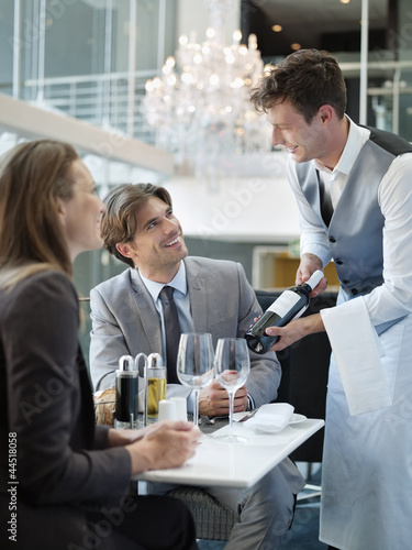 Sommelier presenting wine bottle to couple in restaurant