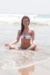 girl in a white bathing suit sits on sand in a lotus pose
