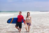 man and the girl with a surfboard go on an ocean coast