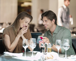 Man with engagement ring proposing to woman in restaurant