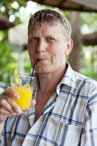 man drinks orange juice in summer cafe