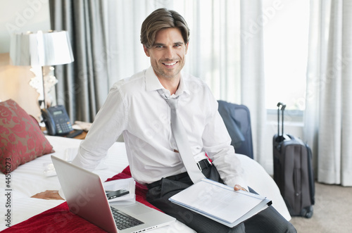 Portrait of smiling businessman with paperwork and laptop on bed in hotel room