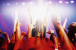 Stage lights shining on audience with arms raised at music concert