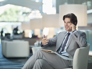 Smiling businessman talking on cell phone in lobby