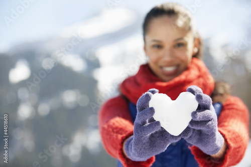 Portrait of smiling woman holding heart-shape snowball