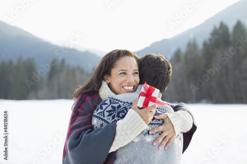 Smiling woman holding Christmas gift and hugging man in snow