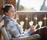 Smiling woman with paper and pen on cabin porch