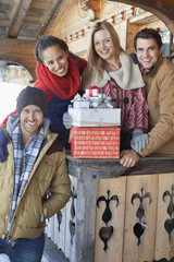 Portrait of smiling couples with Christmas gifts on cabin porch