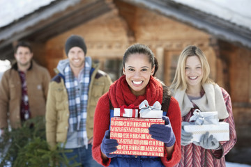 Portrait of smiling couples holding fresh cut Christmas tree and gifts