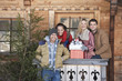 Portrait of smiling couples with fresh cut Christmas tree and gifts in front of cabin