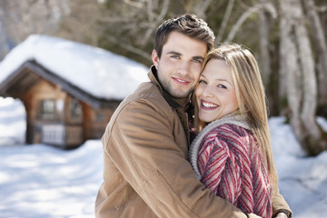 Portrait of smiling couple hugging in front of cabin