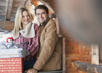 Portrait of smiling couple with Christmas gifts on cabin porch