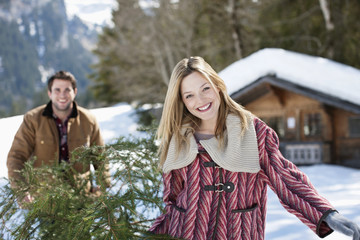 Portrait of smiling couple carrying fresh cut Christmas tree in snow