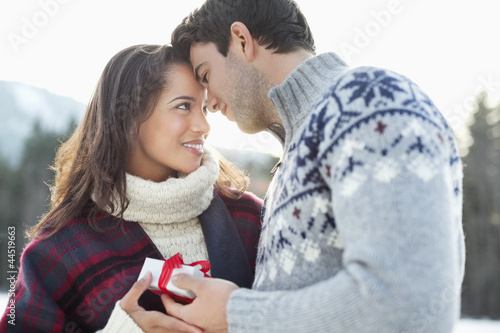Smiling couple face to face with Christmas gift