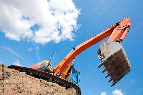 Excavator standing in a ground with raised bucket over sky