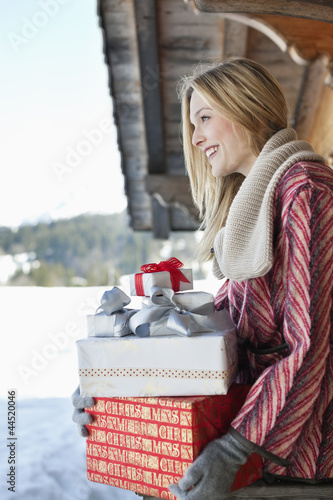 Smiling woman holding Christmas gifts on cabin porch