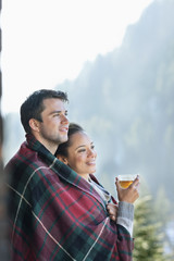 Smiling couple wrapped in a blanket and drinking tea outdoors