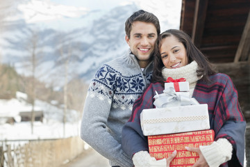 Portrait of smiling couple holding Christmas gifts