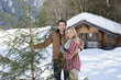 Portrait of smiling couple with fresh cut Christmas tree in front of cabin