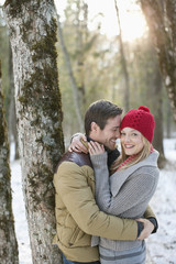 Portrait of smiling couple hugging in snowy woods