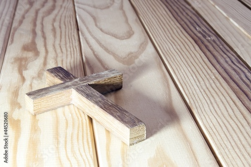 Leinwanddruck Bild cross on wood table background