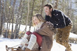 Smiling couple sledding in snow