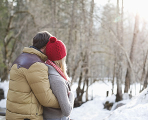 Couple hugging in snowy woods