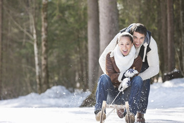 Smiling couple sledding in snowy field