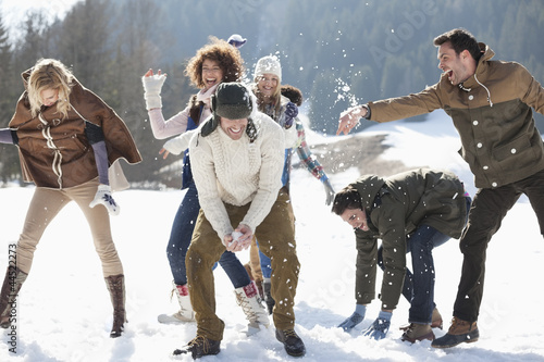 Friends enjoying snowball fight in field