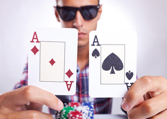 young poker player showing a pair of aces