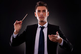 Young businessman directing with a conductor's stick