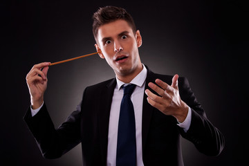 Young conductor sticking his baton in his ear