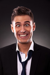 Young businessman with tie undone, making a silly face