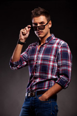 young casual man taking down his sunglasses
