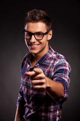 young casual man with spectacles pointing at the camera