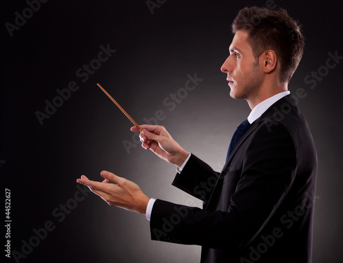 Side view of a young business man directing