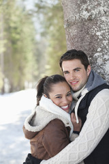 Portrait of smiling couple leaning against tree trunk in snowy woods