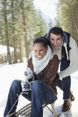 Smiling couple sledding in snowy woods