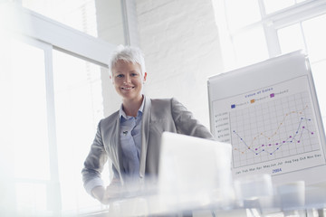 Portrait of smiling businesswoman next to graph in conference room
