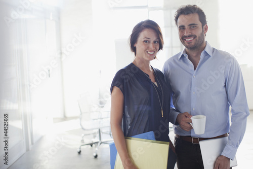 Portrait of smiling businessman and businesswoman in conference room