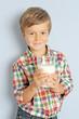 Junge hält ein Glas Milch in der Hand