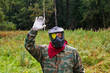 Paintball player with a spot of paint on goggles waving hand